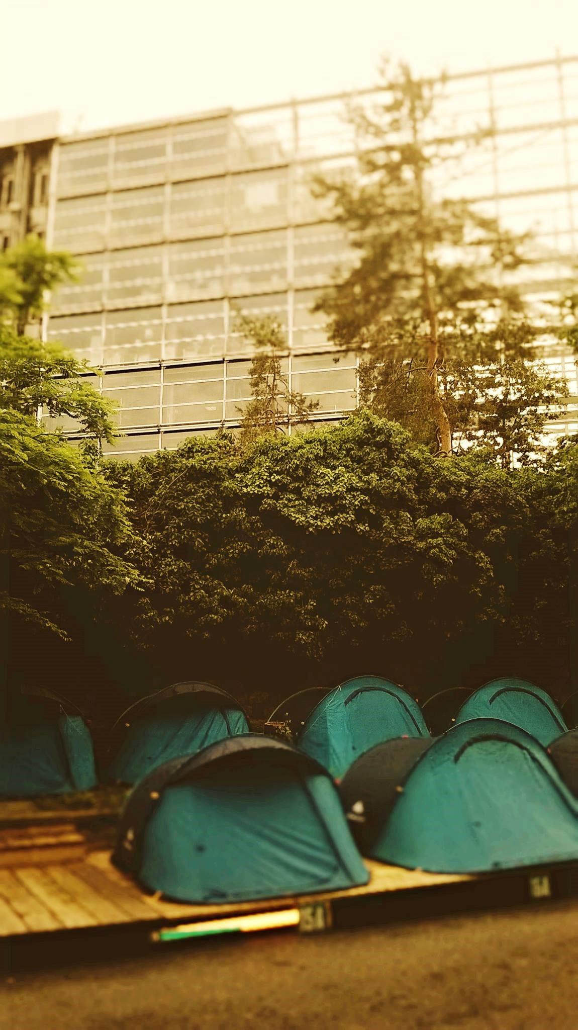 Il progetto Les Grands Voisins a Parigi. Nella foto: il palazzo della Fondation Cartier in alto, le tende di un campeggio in basso.